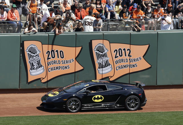 The Batmobile in the AT&T Park outfield with Miles Scott, dressed as Batkid, who threw out the ceremonial first pitch before an opening day baseball game between the San Francisco Giants and the Arizona Diamondbacks in San Francisco, Tuesday, April 8, 2014. On Nov. 15, 2013, Scott, a Northern California boy with leukemia, fought villains and rescued a damsel in distress as a caped crusader through The Greater Bay Area Make-A-Wish Foundation. (AP Photo/Jeff Chiu)