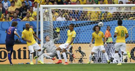 Daley Blind of the Netherlands (L) shoots to score against Brazil during their 2014 World Cup third-place playoff at the Brasilia national stadium in Brasilia July 12, 2014. REUTERS/Ueslei Marcelino