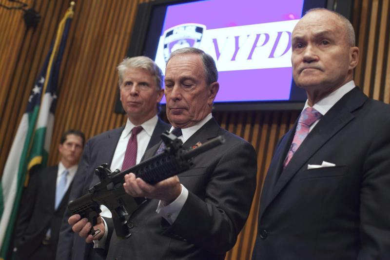 New York City Mayor Bloomberg examines a confiscated gun during a news conference on major firearms trafficking cases, in New York