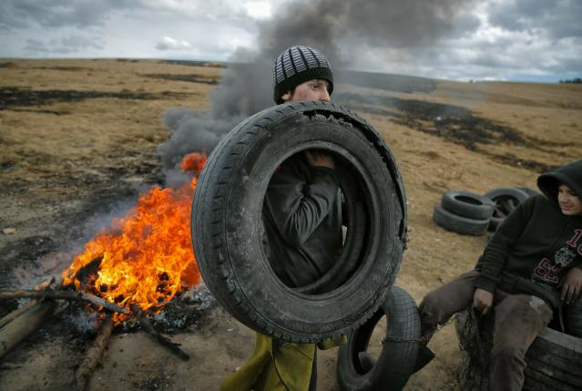In this photo taken on Sunday, March 10, 2019, a boy holds a tire, during a ritual marking the upcoming Clean Monday, the beginning of the Great Lent, 40 days ahead of Orthodox Easter, on the hills surrounding the village of Poplaca, in central Romania's Transylvania region. Romanian villagers burn piles of used tires then spin them in the Transylvanian hills in a ritual they believe will ward off evil spirits as they begin a period of 40 days of abstention, when Orthodox Christians cut out meat, fish, eggs, and dairy. (AP Photo/Vadim Ghirda)