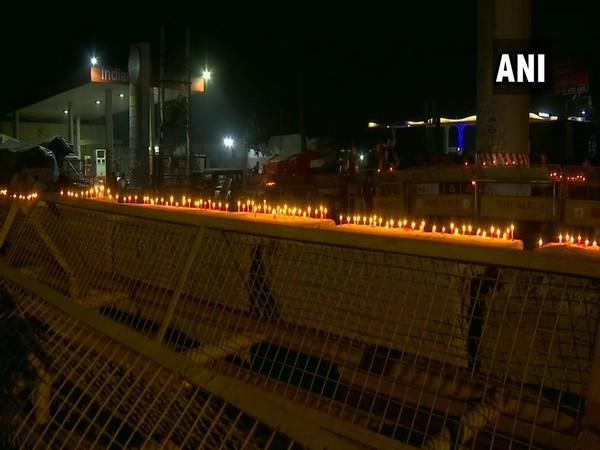 Protestesting farmers lighten up candles on barricades placed by security forces at Tikri border. (Photo/ANI)