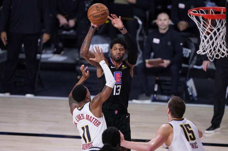 Los Angeles Clippers guard Paul George (13) shoots over Denver Nuggets guard Monte Morris (11) during the second half of an NBA conference semifinal playoff basketball game Tuesday, Sept. 15, 2020, in Lake Buena Vista, Fla. (AP Photo/Mark J. Terrill)