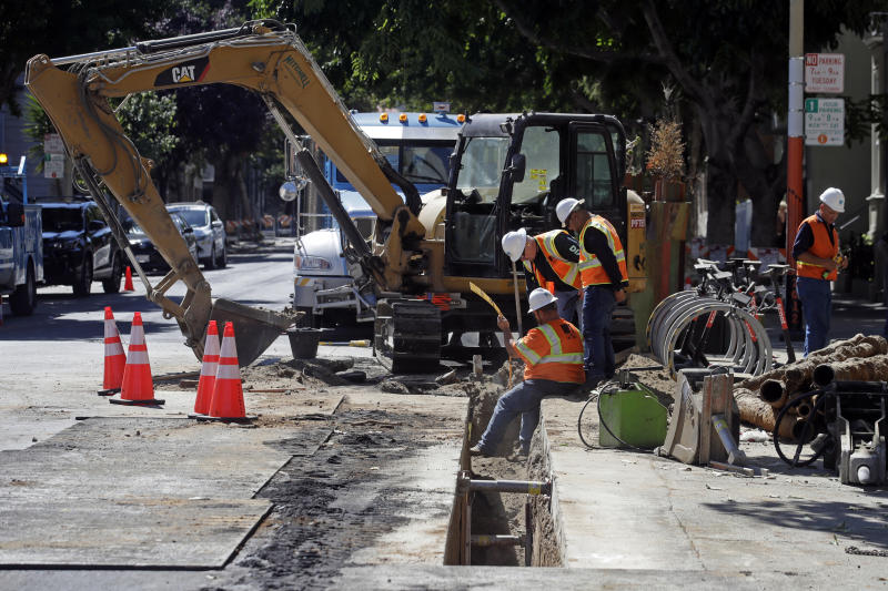This Aug. 15, 2019 photo shows a Pacific Gas & Electric crew working in San Francisco. San Francisco officials are offering to buy Pacific Gas & Electric's power lines and other infrastructure in the city for $2.5 billion. Mayor London Breed and City Attorney Dennis Herrera presented the offer in a letter sent to the utility Friday, Sept. 6, 2019. (AP Photo/Jeff Chiu)