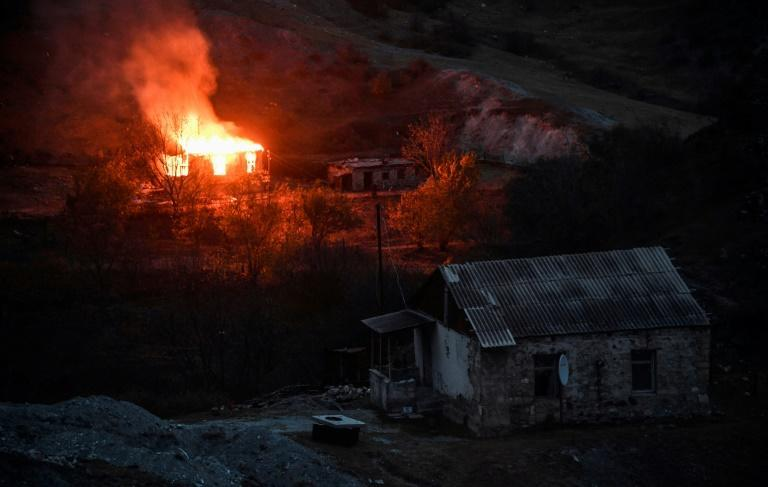 A home burns as ethnic-Armenians leave an area ahead of Azerbaijan taking control in a peace deal
