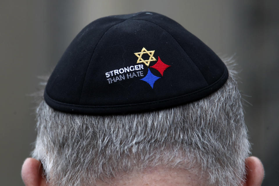 "FILE - In this Sunday, Oct. 27, 2019 file photo, a man wearing a ""Stronger Than Hate"" yarmulke stands outside the Tree of Life synagogue in Pittsburgh on the first anniversary of the shooting at the synagogue, that killed 11 worshippers. On Tuesday, Oct. 27, 2020, as they again mourn those killed two years earlier, they'll also celebrate the resilience that has enabled them to persevere. (AP Photo/Gene J. Puskar)"