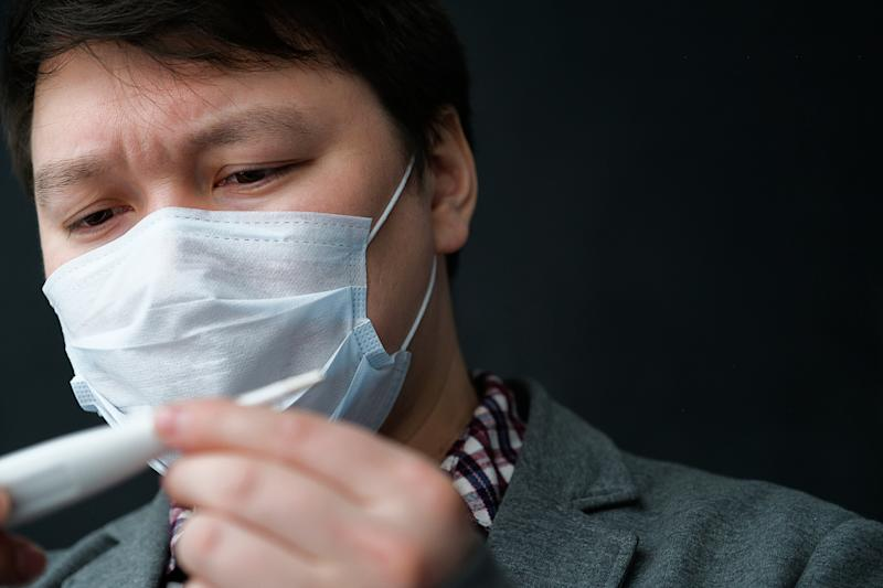 A Flu-infected Asian man in a medical mask looks at a thermometer. The Concept Of Air Pollution, Pneumonia Outbreaks, Coronavirus Epidemics, And The Danger Of Biological Viral Infection.