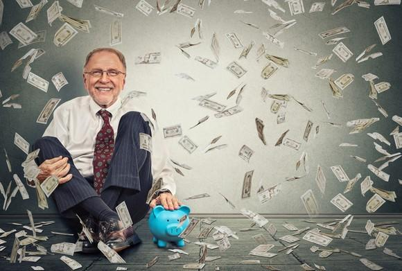 A senior businessman sits with his back to a wall as paper money falls down around him.