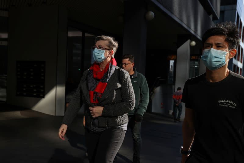People in masks walk through the city centre in Sydney