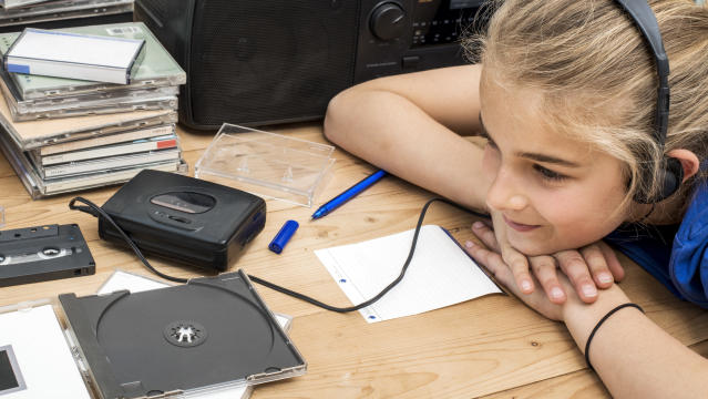 Closeup of young girl listening to nineties music on boombox or CD player