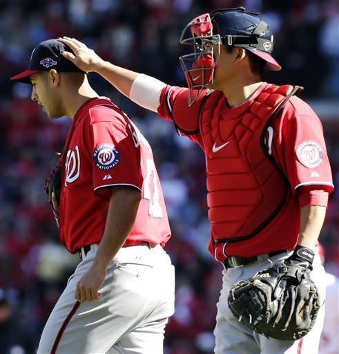 Washington Nationals starting pitcher Gio Gonzalez gets a pat on the head by catcher Kurt Suzuki after walking a batter during the second inning of Game 1 of the National League division baseball series against the St. Louis Cardinals, Sunday, Oct. 7, 2012, in St. Louis. (AP Photo/Charlie Riedel)