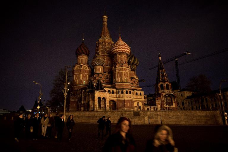 People walk past St. Basil's Cathedral with its lights off as part of the Earth Hour environmental campaign in central Moscow on March 28, 2015
