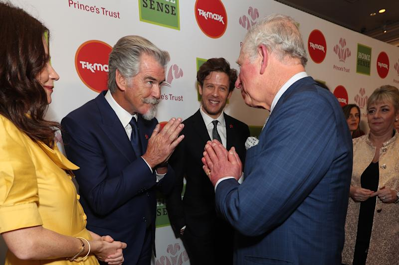 The Prince of Wales greets Pierce Brosnan with a Namaste gesture as he arrives at the annual Prince's Trust Awards 2020 held at the London Palladium.