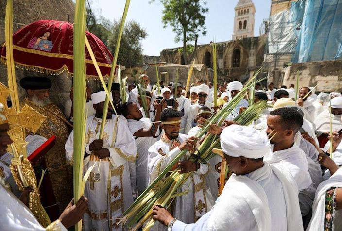 Clergymen dressed in white and carrying gold crosses handle palm reeds ahead of the Church service.