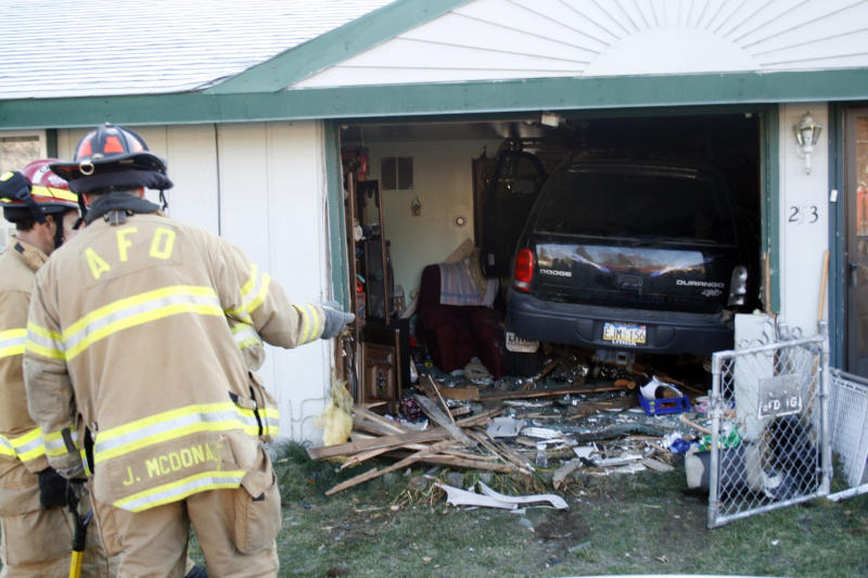 Firemen look over a vehicle that drove completely into a home in Anchorage, Alaska, on Tuesday, Oct. 11, 2011, barely missing the homeowner, who was sitting in a chair that the SUV missed by inches. The driver was taken to the hospital with minor injuries; the homeowner was skaken up but unhurt. (AP Photo/Mark Thiessen)