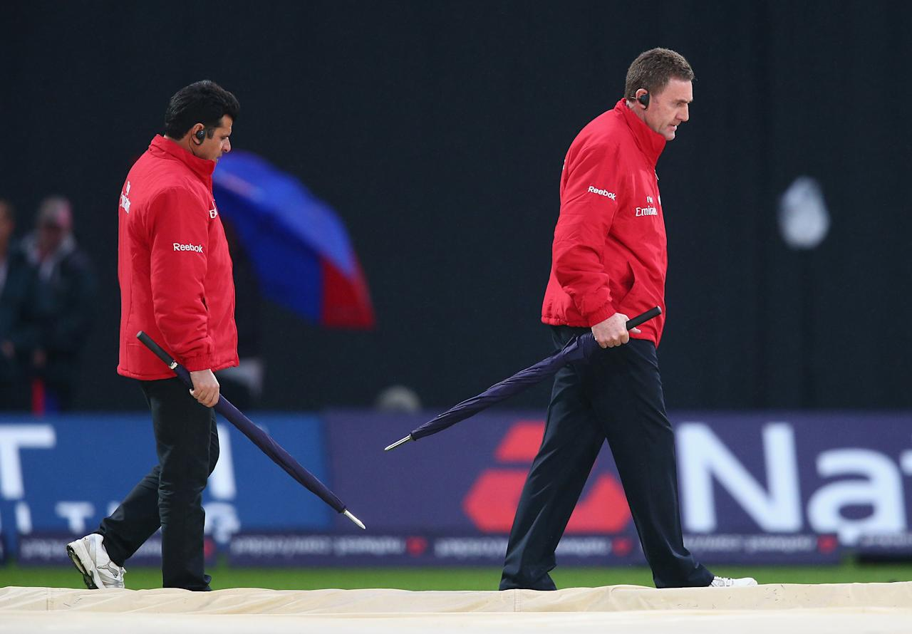 BIRMINGHAM, ENGLAND - SEPTEMBER 11:  Umpires Rob Bailey and Aleem Dar inspect the pitch as rain stops play during the third NatWest One Day International Series match between England and Australia at Edgbaston on September 11, 2013 in Birmingham, England.  (Photo by Clive Mason/Getty Images)