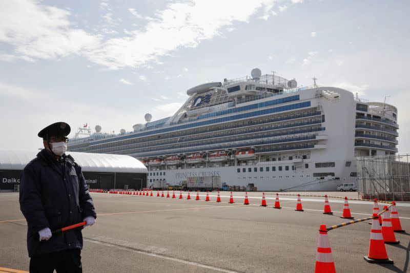 A man wearing a mask stands guard at the port next to the cruise ship Diamond Princess at Daikoku Pier Cruise Terminal in Yokohama, south of Tokyo