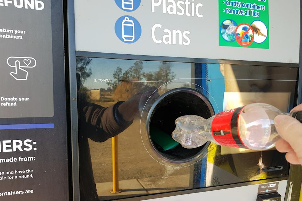 A hand drops a bottle into a chute at a NSW Government Return and Earn centre. Source: Getty Images
