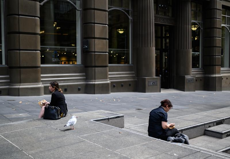 Two people sit a distance apart eating lunch in Martin Place, Sydney