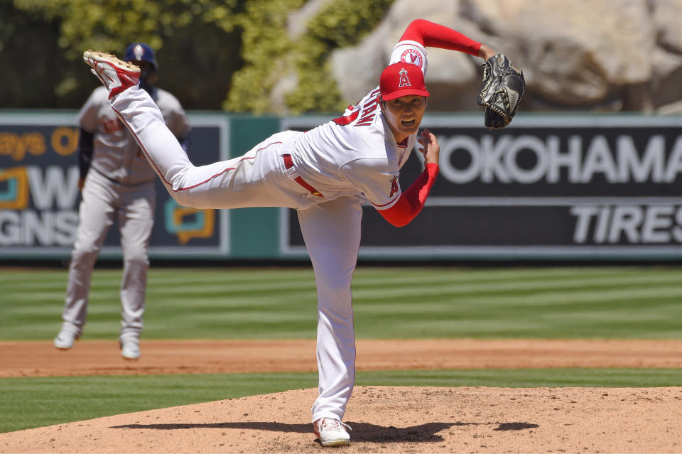 Los Angeles Angels designated hitter Shohei Ohtani, right, of Japan, throws to the plate as Houston Astros' Yuli Gurriel stands at second during the second inning of a baseball game Sunday, Aug. 2, 2020, in Anaheim, Calif. (AP Photo/Mark J. Terrill)