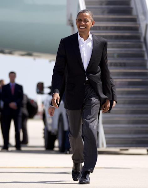 President Barack Obama walks to greet people waiting for him on the tarmac as he arrives at O'Hare International Airport on Air Force One, Saturday, Aug. 11, 2012, in Chicago. (AP Photo/Carolyn Kaster)
