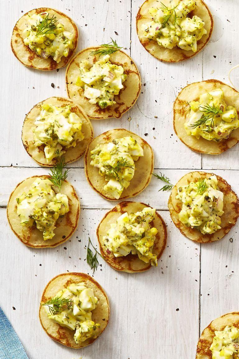 """<p>These mini pancakes give you the perfect amount of egg salad per bite, but that won't stop your guests from asking for seconds.</p><p><em><a href=""""https://www.goodhousekeeping.com/food-recipes/easy/a26767989/egg-salad-blini-bites-recipe/"""" rel=""""nofollow noopener"""" target=""""_blank"""" data-ylk=""""slk:Get the recipe for Egg Salad Blini Bites »"""" class=""""link rapid-noclick-resp"""">Get the recipe for Egg Salad Blini Bites »</a></em></p>"""