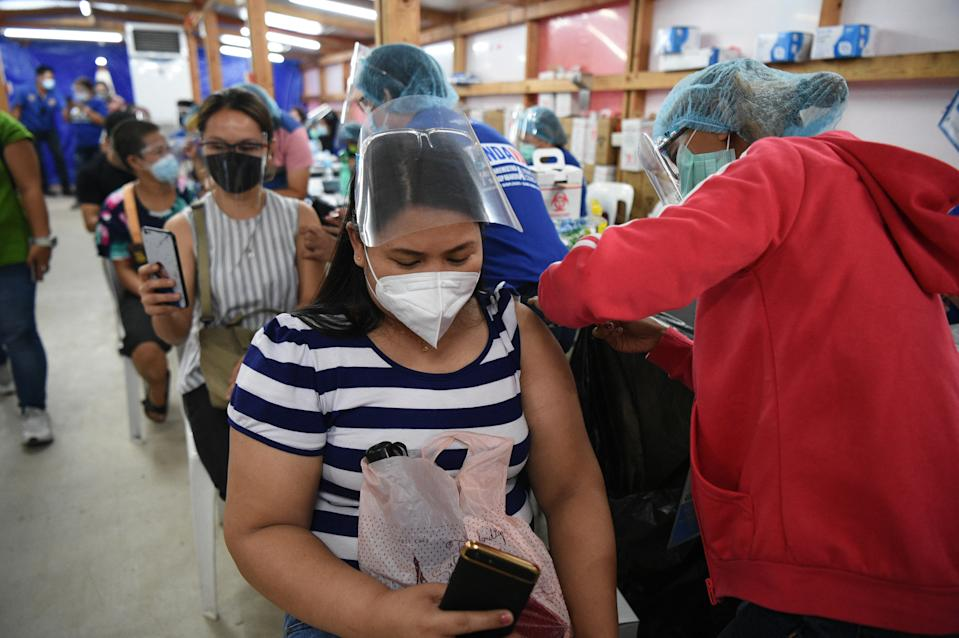 Health workers innoculate residents with Gamaleya National Center of Epidemiology and Microbiology's Sputnik V Covid-19 vaccines in Mandaluyong City, suburban Manila on July 15, 2021. (Photo: TED ALJIBE/AFP via Getty Images)