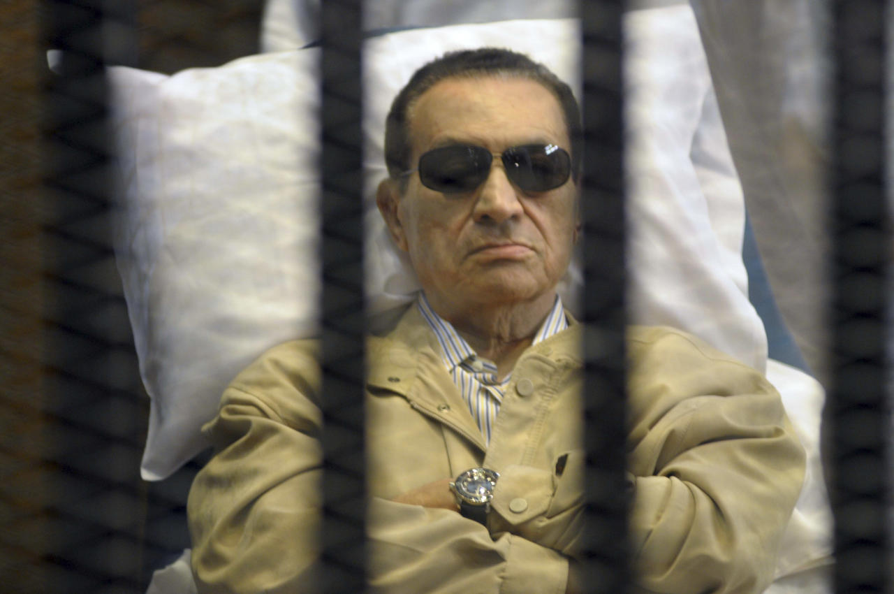 Egypt's ex-President Hosni Mubarak lays on a gurney inside a barred cage in the police academy courthouse in Cairo, Egypt, Saturday, June 2, 2012. Mubarak was sentenced to life in prison Saturday for his role in the killing of protesters during last year's revolution that forced him from power, a verdict that caps a stunning fall from grace for a man who ruled the country as his personal fiefdom for nearly three decades.(AP Photo)