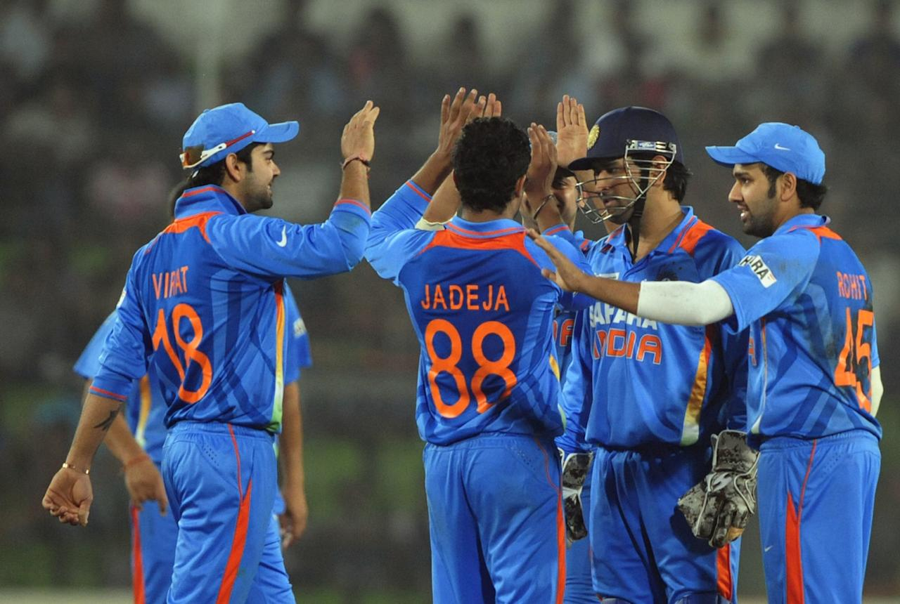 Indian cricketers celebrate after the dismissal of Bangladeshi batsman Jahurul Islam (unseen) during the one day international (ODI) Asia Cup cricket match between India and Bangladesh at the Sher-e-Bangla National Cricket Stadium in Dhaka on March 16, 2012. India's Sachin Tendulkar became the first batsman in history to score 100 international centuries, adding another milestone in his record-breaking career. AFP PHOTO/Munir uz ZAMAN (Photo credit should read MUNIR UZ ZAMAN/AFP/Getty Images)