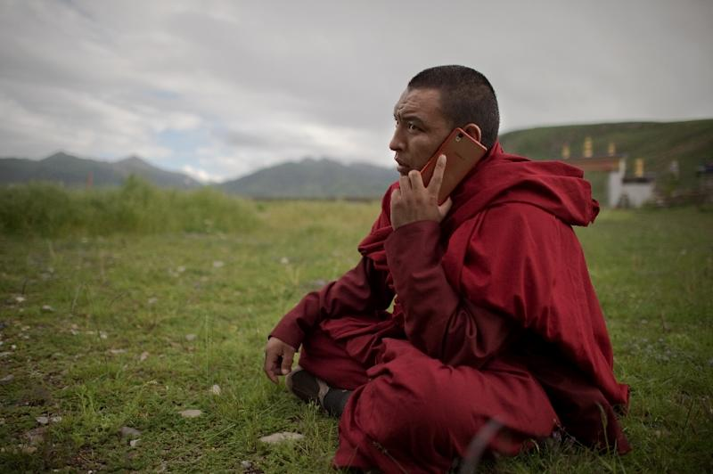 A Buddhist monk talks on his smartphone as he sits on the grassland of the Tibetan Plateau in Yushu County (AFP Photo/Nicolas Asfouri)