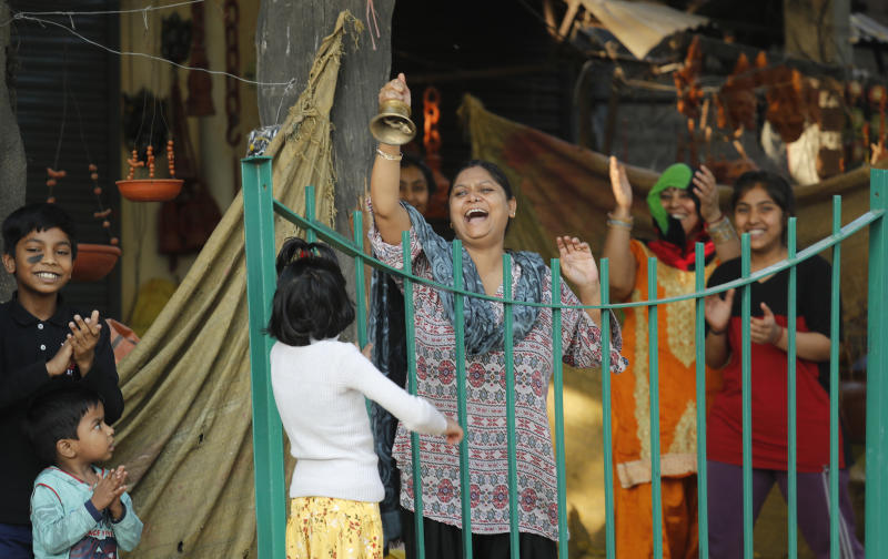 """FILE - In this Sunday, March 22, 2020, file photo, families of roadside shopkeepers ring bell and clap to cheer health workers during 14-hour """"people's curfew"""" called by Prime Minister Narendra Modi in order to stem the rising coronavirus caseload, in New Delhi, India. As India and other South Asian nations brace for the likely spread of the virus, they are facing another battle: reams of misinformation, misleading rumors and false claims. The WhatsApp messaging app was flooded with claims that """"cosmic level sound waves"""" generated by a collective cheer Modi had asked the country of 1.3 billion to participate in last Sunday had weakened the virus in India. (AP Photo/Manish Swarup, File)"""