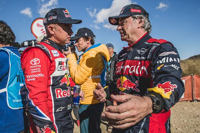 "#305 JCW X-Raid Team: Carlos Sainz with #304 Toyota Gazoo Racing: Giniel De Villiers <span class=""copyright"">Red Bull Content Pool</span>"