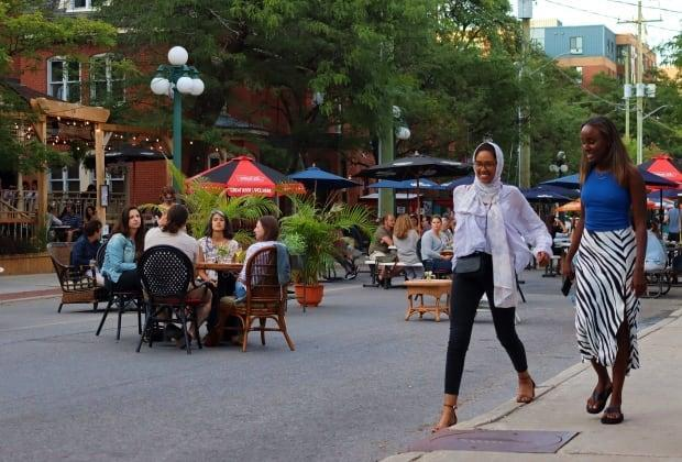 People eat and drink at tables set up on a stretch of Somerset Street West over the weekend. The street was closed to cars to allow restaurants to seat more people on patios. (Trevor Pritchard/CBC - image credit)
