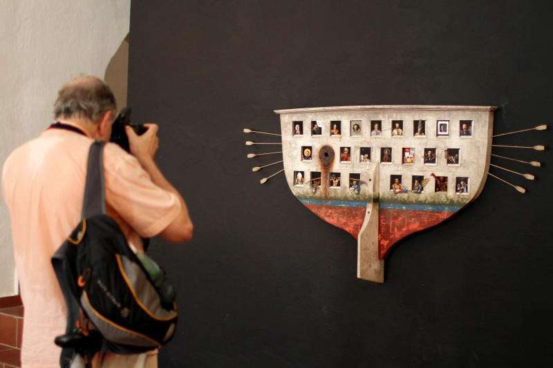 """A visitor takes a picture of """"My Ark"""" by Cuban artist Ruben Alpizar at the San Carlos de La Cabana fortress as part of the 11th Havana Biennial exhibition in Havana, Cuba, Friday, May 25, 2012. The piece was bought by an American art collector during the month long art event. An unusually large delegation of American artists, curators, collectors and fans were accredited to attend the Biennial, organizers say. Unlike with other island goods, it's perfectly legal for Americans to buy Cuban art, which is covered under an exemption to the 50-year-old U.S. embargo allowing the purchase of """"informational materials.""""  (AP Photo/Franklin Reyes)"""