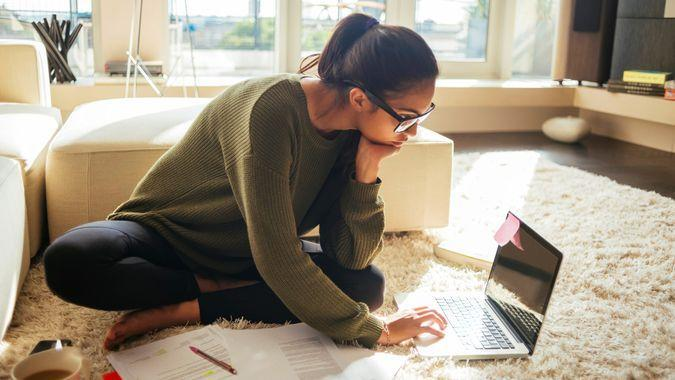 young woman studying and working on her laptop,sitting on the carpet in the living room,nice sunny day.