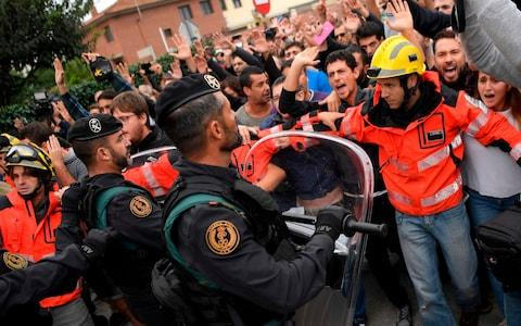 Firemen try to hold a group of people in front of Spanish Guardia Civil officers outside a polling station in San Julia de Ramis - Credit: LUIS GENE/AFP/Getty Images