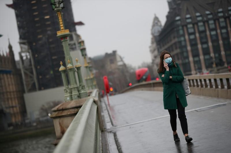 FILE PHOTO: A woman on Westminster bridge wearing a protective face mask