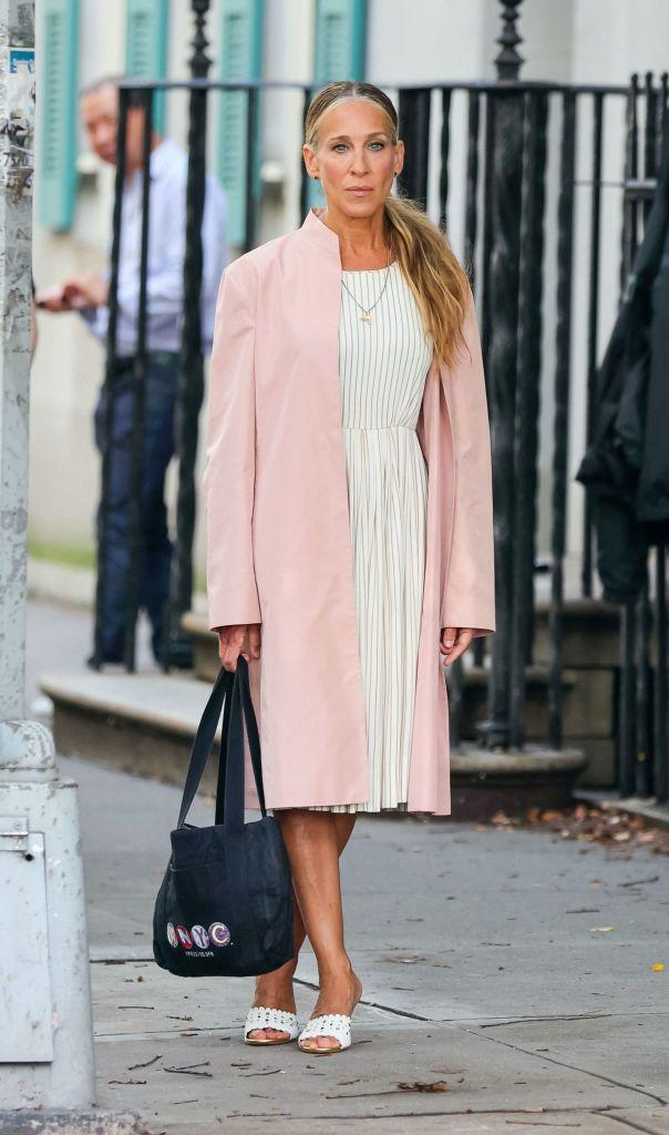 <p>Just like in the opening credits of Sex And The City, Carrie is wearing baby pink again with a white pleated midi dress and mule heels. </p><p>Staying true to her journalistic routes, the black tote bag Carrie is carrying (or, carrie-ing) has the acronym WNYC embroidered in which is a nonprofit New York public radio station.</p>