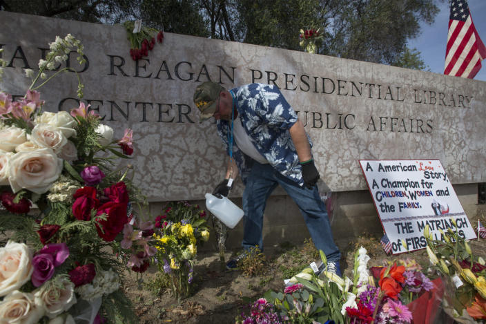 <p>Dane Senser waters flowers at a makeshift memorial outside the Ronald Reagan Presidential Library as former first lady Nancy Reagan lies in repose, on March 9, 2016, in Simi Valley, Calif. The first lady will be buried next to her husband at the library.<i> (Photo: David McNew/Getty Images)</i></p>