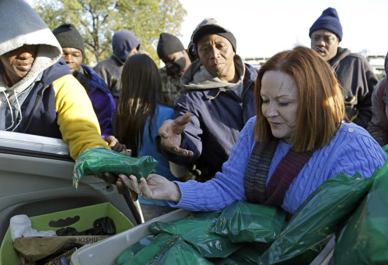In this Dec. 10, 2013 photo, Jacquie Brennan, right, of A Simple Thread, hands out support kits to a group of homeless people in Houston. Brennan's volunteer group received a large donation from The Original OKRA Charity Saloon, a Houston bar that gives 100 percent of its profits to charity. (AP Photo/Pat Sullivan)