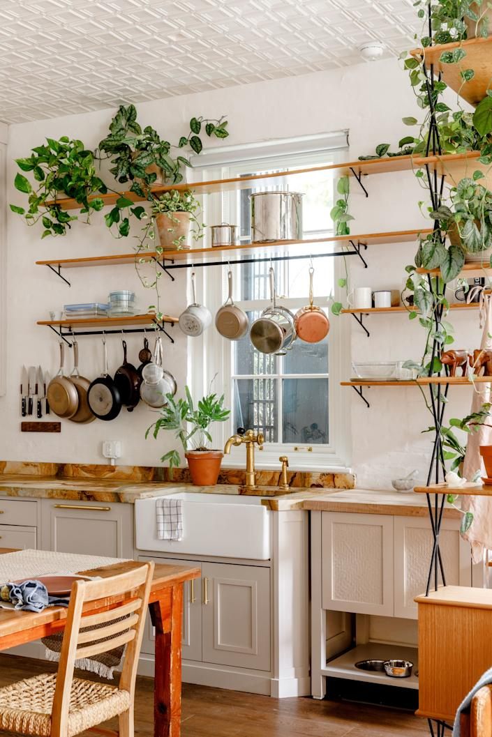 Open shelving stocked with plants gives the kitchen an airy, outdoor feel. The cabinets below are painted in Elephant's Breath from Farrow & Ball and topped with quartzite counters from New York Stone.