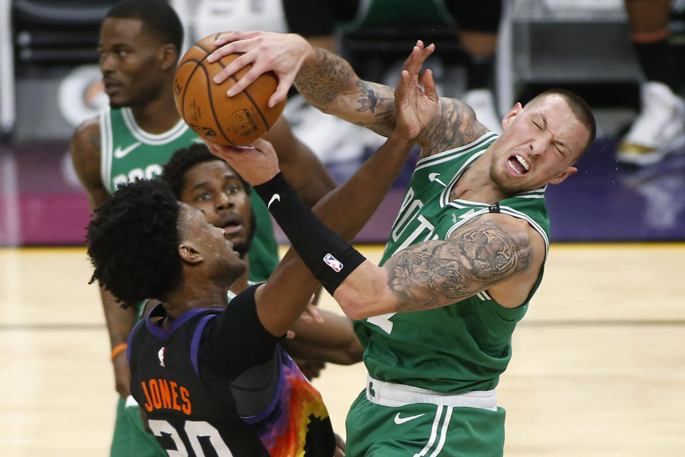 Boston Celtics forward Daniel Theis, right, is fouled by Phoenix Suns center Damian Jones, left, as he grabs a rebound during the first half of an NBA basketball game, Sunday, Feb. 7, 2021, in Phoenix. (AP Photo/Ralph Freso)