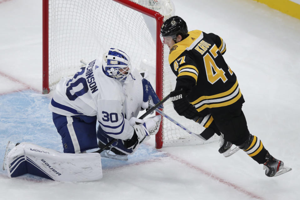 Toronto Maple Leafs goaltender Michael Hutchinson (30) grabs the stick of Boston Bruins defenseman Torey Krug during the first period of an NHL hockey game in Boston, Tuesday, Oct. 22, 2019. (AP Photo/Charles Krupa)