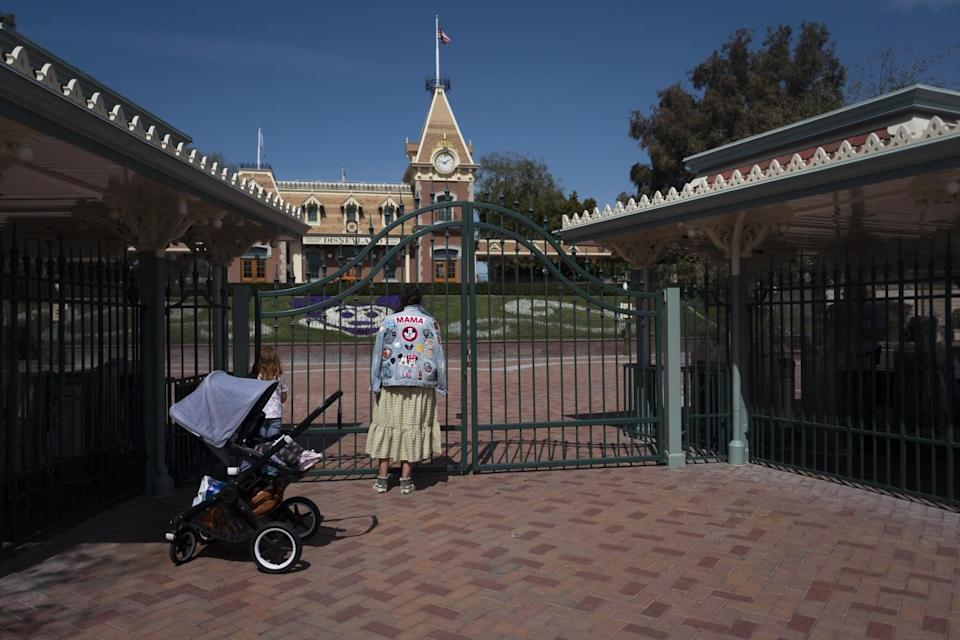 A person with a stroller stands outside Disneyland's gates