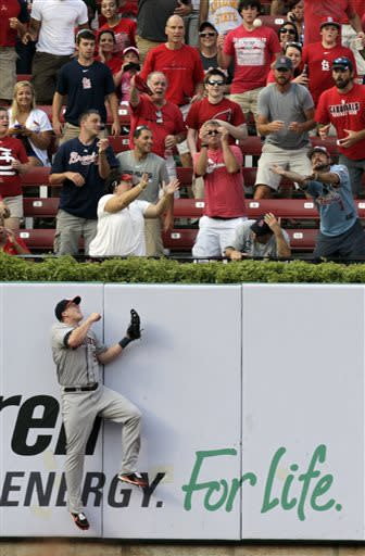 Houston Astros left fielder Marc Krauss collides with the wall as St. Louis Cardinals fans reach for a home run by St. Louis Cardinals' Matt Holliday in the first inning of a baseball game, Tuesday, July 9, 2013, in St. Louis.(AP Photo/Tom Gannam)