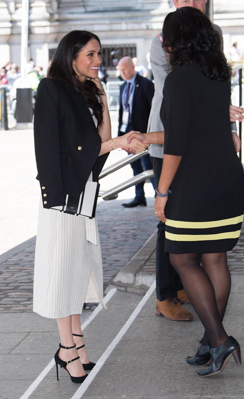 <p>Meghan Markle greeted attendees of the Commonwealth Youth Forum with a power blazer draped over her shoulders. </p>