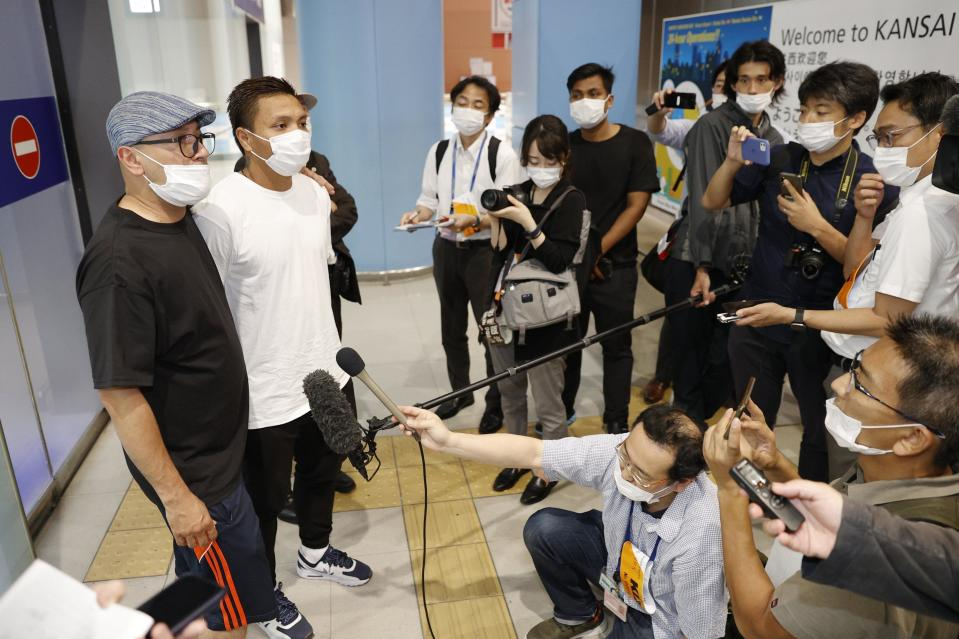 Pyae Lyan Aung, second from left, a member of the Myanmar national Olympic team who raised a three-finger salute during a qualifying match for the 2022 World Cup in late May, speaks to media as he arrives at the Kansai International Airport in Osaka Prefecture, Japan, Thursday June 17, 2021. Pyae Lyan Aung has refused to return home and is seeking asylum, a request the government was considering taking into account unrest in his country following a coup.(Kyodo News via AP)