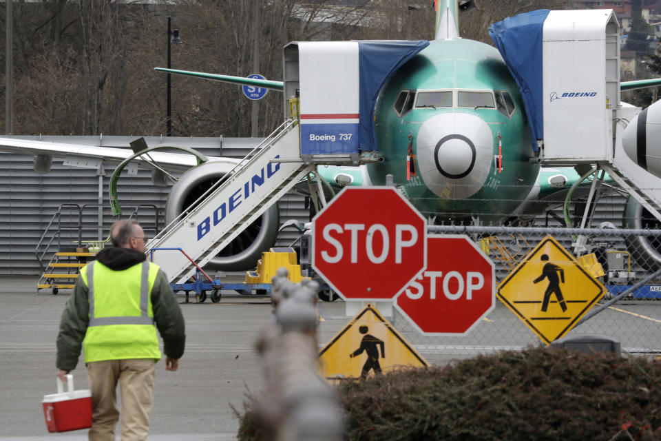 FILE - In this Monday, Dec. 16, 2019 file photo, a Boeing worker walks in view of a 737 MAX jet in Renton, Wash. Shares of Boeing fell before the opening bell on a report that the company may cut production of its troubled 737 MAX or even end production all together. (AP Photo/Elaine Thompson)