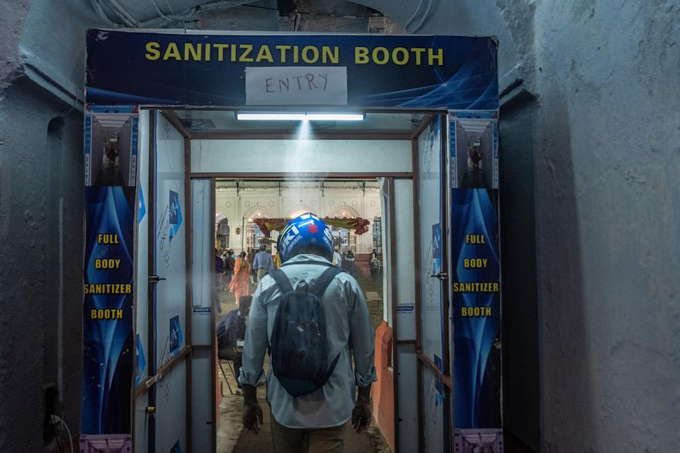 A man goes through a sanitization tunnel at Sobhabajar, Rajbhari.