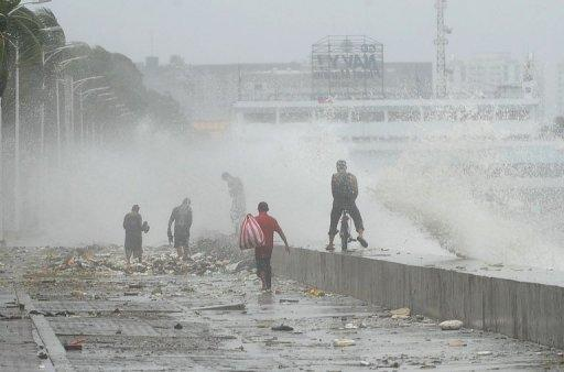 Large waves crash over a promenade at Manila's Roxas boulevard on July 30. At least three people were killed and millions were left without power as Tropical Storm Saola turned into a typhoon, bringing heavy rains to large parts of the Philippines