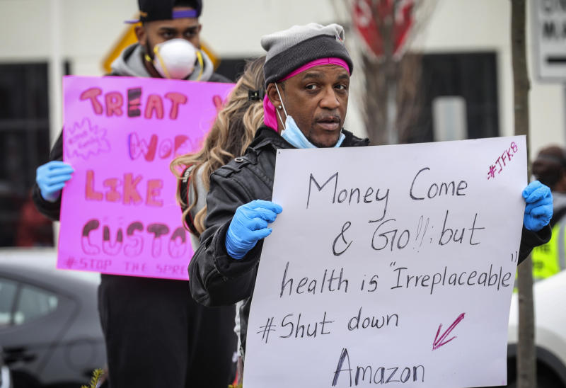 FILE - In this March 30, 2020, file photo, workers at an Amazon fulfillment center in Staten Island, N.Y., protest conditions in the company's warehouse. A month later, even after Amazon scrambled to provide masks and gloves and check employees' temperatures, Amazon workers have continued scattered walkouts across the country to protest what they say are still-risky conditions in warehouses where workers have had the virus. (AP Photo/Bebeto Matthews, File)